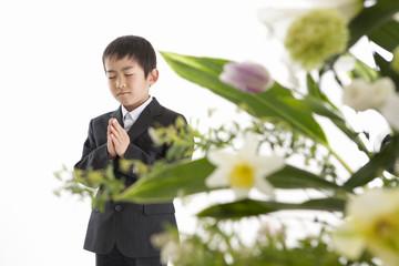 合掌する喪服姿の少年と祭壇の花