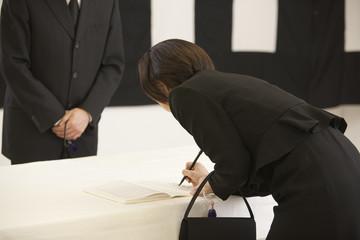 記帳をする喪服姿の女性と受付の男性