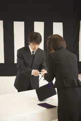 香典袋を手渡す喪服姿の女性と受付の男性