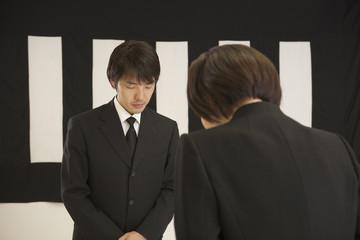 葬儀の受付で挨拶をする喪服姿の男女