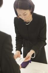 香典袋を手渡す喪服姿の女性