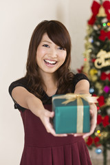 クリスマスプレゼントを差し出す若い女性