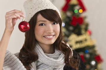 クリスマスツリーのオーナメントを持つ女性