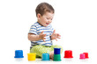 funny baby playing with colourful cup toys on floor, isolated ov