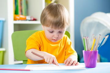 child drawing with pencils indoors