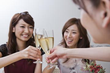 クリスマスパーティーで乾杯する女性三人