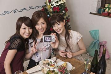 クリスマスパーティーで写真を撮る女性三人