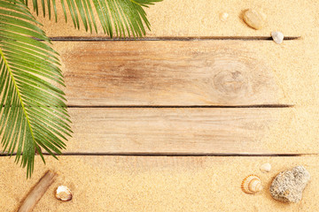 Palm tree leaves and sand on wood background