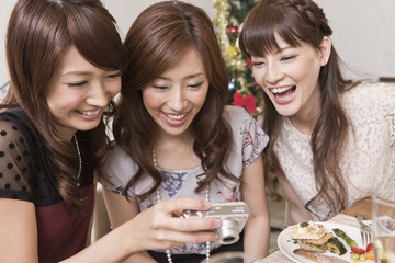 クリスマスパーティーで写真を見る女性三人