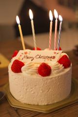 ろうそくの火を点けたクリスマスケーキ
