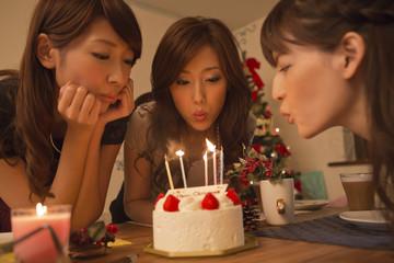 ケーキのキャンドルの火を吹き消す女性三人