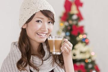 カップを持つ女性とクリスマスツリー