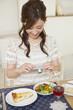 デジタルカメラで料理の写真を撮る女性