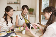 女子会でワインボトルを見る女性三人