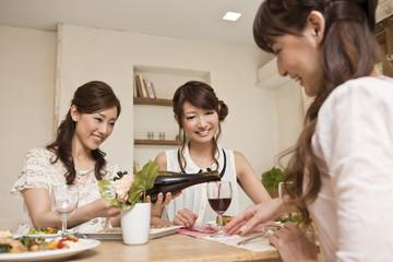 女子会でワインを注ぐ女性三人