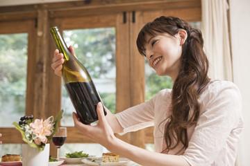 ワインボトルを見る女性