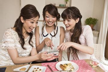 女子会で写真を見る女性三人