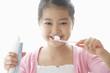 歯ブラシを持って見つめる女の子