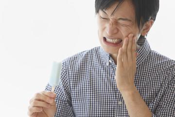 歯痛に顔をゆがめる若い男性
