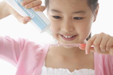 歯磨き粉を歯ブラシに付ける女の子