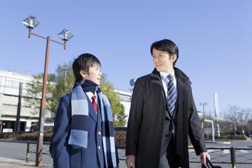 中年男性と並んで歩く男子中学生