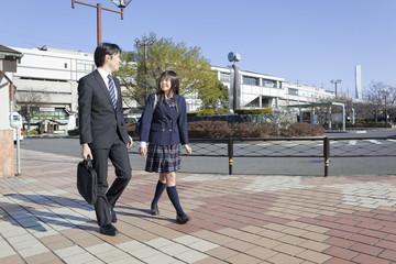 中年男性と並んで歩く女子高校生