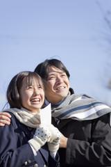 喜ぶ女子高校生と肩を抱く中年男性