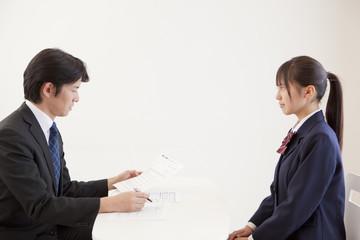 面接で向き合う女子高校生と中年男性