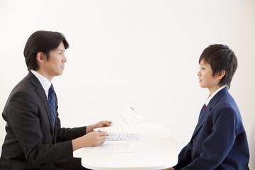 面接で向き合う男子中学生と中年男性