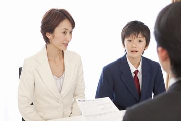 面接で話す男子中学生と中年女性
