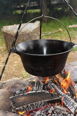 big metal pot on camp fire