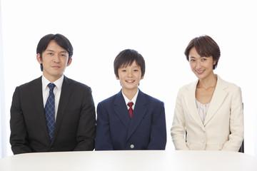 並んで座る笑顔の中年男女と男子中学生