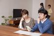 通帳と家計簿を眺めて考える中年男女