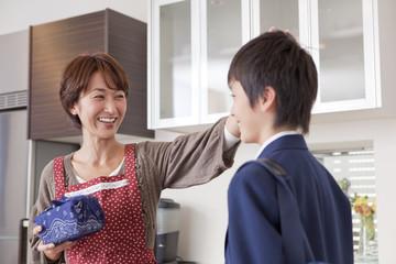 中学生の息子の頭を撫でる母親