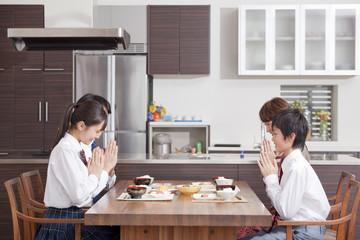 食事の挨拶をする学生の子供と両親