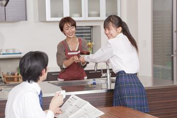 食事の後片付けをする女子高校生と両親