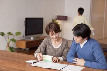 通帳と家計簿を眺めて相談する中年男女
