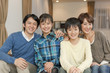 ソファに座る笑顔の学生と両親