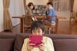 ゲームに熱中する男子中学生と眺める両親