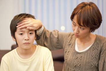 中学生の息子の熱を確認する母親