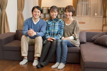 ソファに座る笑顔の女子高校生と両親
