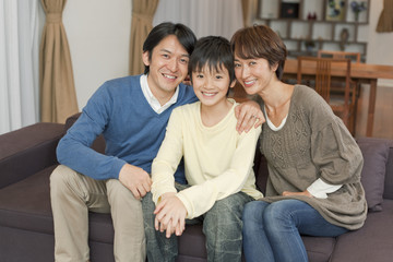 ソファに座る笑顔の男子中学生と両親