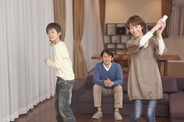 テレビゲームで遊ぶ男子中学生と両親