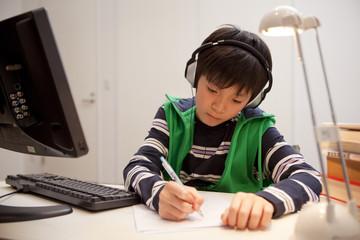 ヘッドホンを付けて勉強する男子中学生