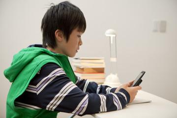 携帯電話を操作する男子中学生