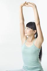 腕を上に伸ばす日本人女性