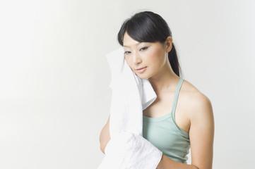 タオルで汗を拭く日本人女性