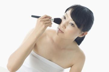 フェイスブラシを頬に当てる日本人女性