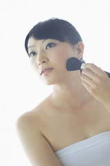 フェイスブラシで化粧をする日本人女性