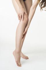 屈んで膝下を触る日本人女性